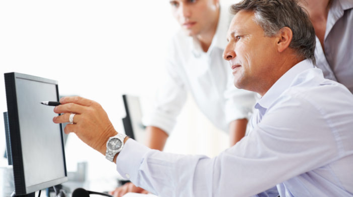 Mature business man discussing project with his colleagues and pointing at computer screen